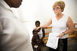 Dr. Pat Wolff confers with nurse Marie Fleurese Gourges over a Haitian medika mamba patient. - JENNIFER SILVERBERG