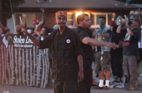 In this August 14 photo, Olajuwon Ali, left, helps direct traffic during a celebratory protest in Ferguson. Ali, whose legal name is Olajuwon Davis, was indicted last week on weapons charges. - DANNY WICENTOWSKI