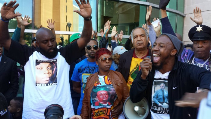 "Michael Brown Sr. (L) gives the ""Hands Up, Don't Shoot"" sign during a protest with Lesley McSpadden, Michael Brown's mother, and Pastor Carlton Lee. - JESSICA LUSSENHOP"