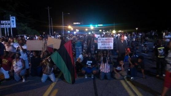 Protesters got on their knees in front of a police barricade on West Florissant Avenue. - RAY DOWNS