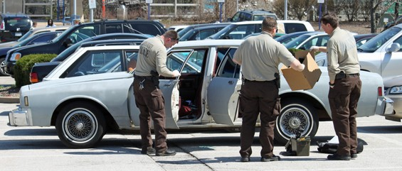 St. Louis County police investigate a primer gray Chevrolet Impala involved in shooting. - PHOTO: AMIR KURTOVIC