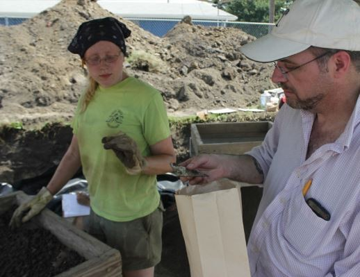 Joseph Galloy examines a 19th-century piece of glass uncovered at the dig site. - DANNY WICENTOWSKI