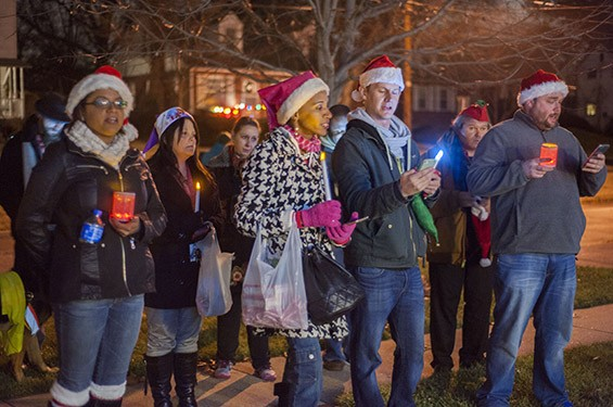 Maxine Harris (in pink) and other carolers sing outside of a Ferguson resident's home.