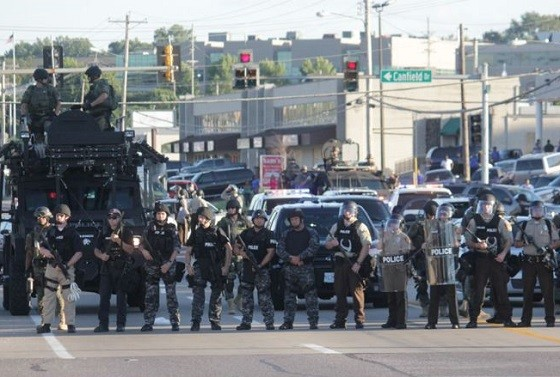 A line of police officers positioned just south of the burned-out Ferguson Quiktrip. - DANNY WICENTOWSKI
