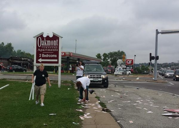 Volunteers clean after riots in Ferguson Sunday night as a news crew looks on. - JESSICA LUSSENHOP
