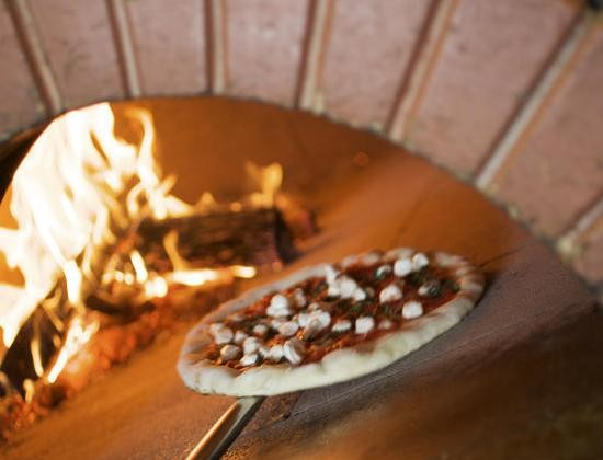 A pizza goes into the oven at Peel Wood Fired Pizza in Edwardsville. - JENNIFER SILVERBERG