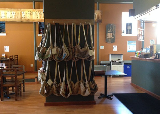 Totes made from recycled coffee bags for sale inside the cafe.   Nancy Stiles