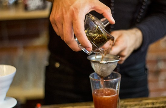 Pouring freshly brewed tea into the mix.