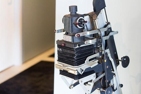 A vintage photo enlarger occupies one corner of the room as decoration.