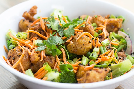 """Orange Cauliflower"" with stir-fried vegetables, green onion, cilantro, black sesame seeds, shredded carrots, brown rice and orange-sesame sauce."