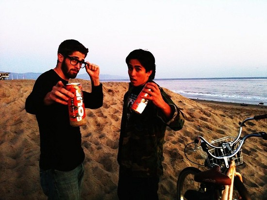 Drink of the Week is not acquainted with these hipsters, nor do we recognize the beach. But we're betting the Four Loko they've got is the original regular, not the reformulated unleaded. - IMAGE VIA