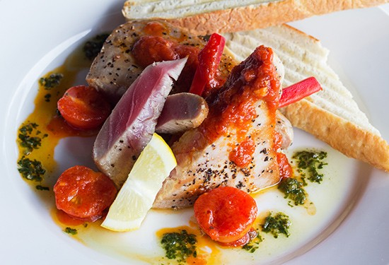 Grilled Ahi tuna with cherry tomatoes, pesto and housemade bread.