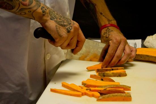 Sous chef David Anderson hand cuts sweet potato fries. - MABEL SUEN