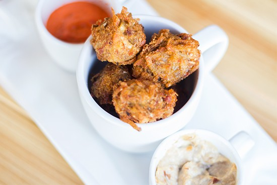 """""""Tots"""" appetizer made with potato and pork served with caramelized-shallot sauce and fire-roasted jalapeno sauce."""