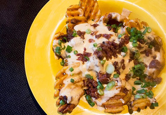 """Roadhouse fries"" with waffle fries topped with pulled pork, bacon, cheddar cheese sauce and scallions."