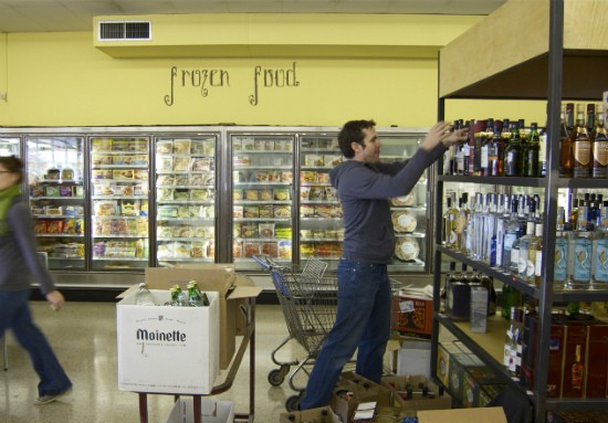 Co-owner Patrick Horine stocks spirits at the new Local Harvest Grocery in Kirkwood. - LIZ MILLER