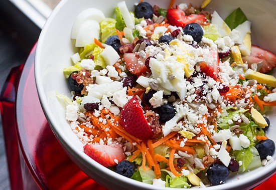 A build-your-own salad with berries, carrots, egg, feta cheese and more.