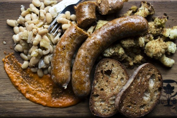 Hungarian bratwurst alongside roasted cauliflower, cider marrow beans, wheat toast and romesco sauce. - JENNIFER SILVERBERG