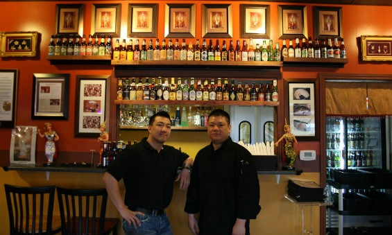 Brothers Tommy (left) and Scott (right) Truong in front of Pearl Cafe's beer selection - CHRISSY WILMES