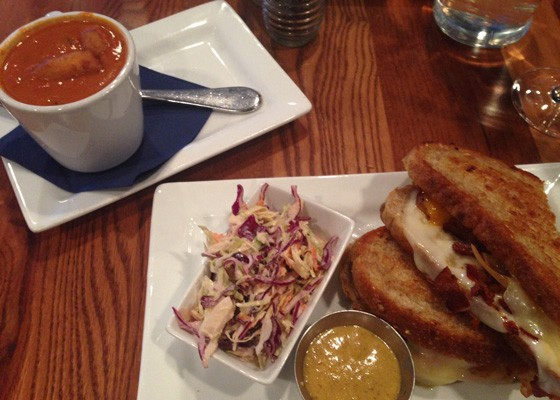 Grilled cheese topped with provolone, cheddar, swiss, bacon, and caramelized apples and onion plus tomato soup.   Nancy Stiles