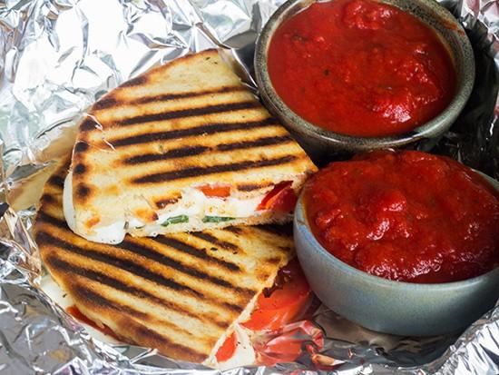 "A ""Pizzanini"" with fresh marinated mozzarella, roma tomatoes, fresh basil and housemade marinara."