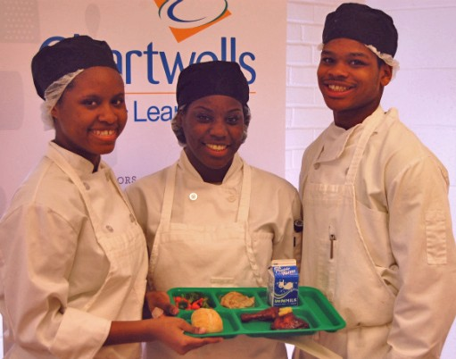 The winning team of student chefs in St. Louis' Healthy Schools Campaign Cooking up Change contest pose with their first-place meal. - IMAGE VIA
