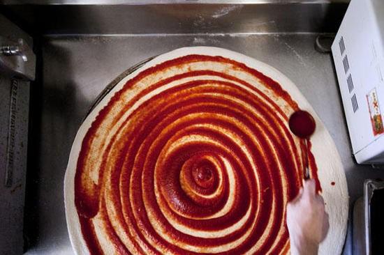 Saucing a big pie at Mr. X Pizza. - JENNIFER SILVERBERG