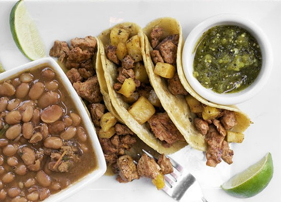 Tacos al pastor at Milagro Modern Mexican, with chile-marinated pork tenderloin with grilled pineapple and cilantro in homemade corn tortillas, served with salsa verde and a side of Mexican beans and rice. - JENNIFER SILVERBERG