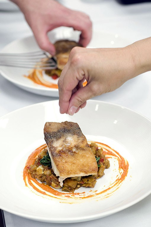 The final touches to this Wild Striped bass are made before two lucky diners get the pleasure. See more photos from Fond. - PHOTO: JENNIFER SILVERBERG