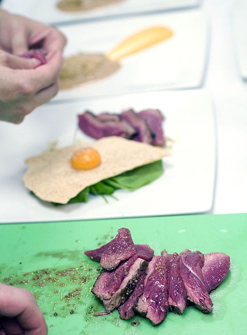 The Salt-crusted Beef being plated. It is served with arugula, egg yolk, black pepper vinaigrette and cracker.  See more photos from the kitchen at Fond. - PHOTO: JENNIFER SILVERBERG