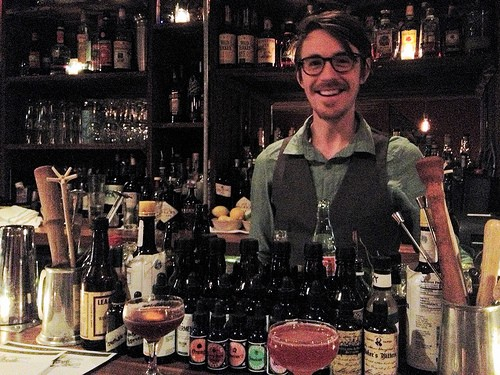 Burton poses behind a selection of bitters. The Blood & Sand cocktail is on the left, the Jack Rose is the pink drink near center. - JAIME LEES