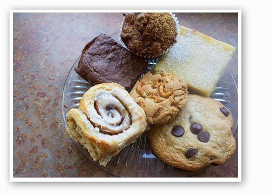 Clockwise from bottom left: cinnamon roll, brownie, banana muffin, lemon bar, chocolate chip cookie and pretzel white chocolate chip cookie.   Mabel Suen