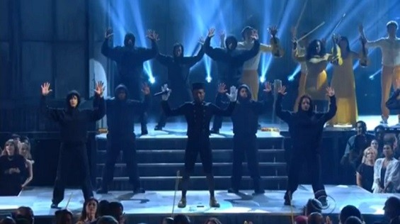 Pharrell's backup dancers wore black hooded sweatshirts to honor Trayvon Martin, and also raised their hands in a familiar pose. - SCREENSHOT VIA CBS
