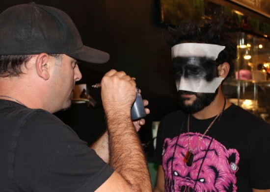 Chris Sabatino, owner of Art Monster, getting airbrushed to finalize his costume. - CASSIE KOHLER