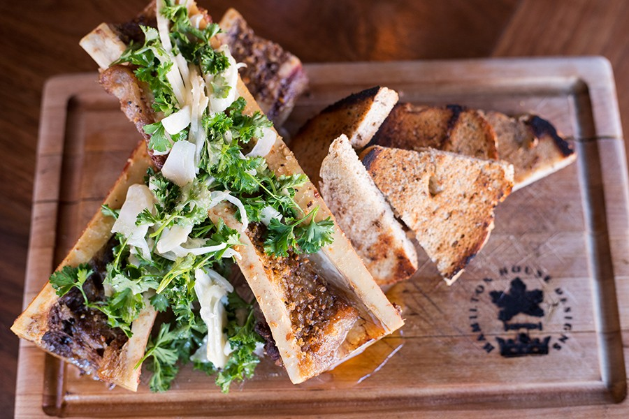 Roasted bone marrow is served with a parsley-fennel salad. - MABEL SUEN
