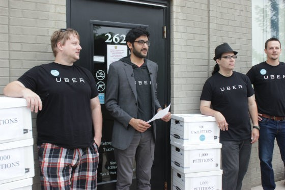 Uber general manager Sagar Shah stands with Uber drivers outside of the Metropolitan Taxicab Commission to deliver signed petitions and comments from the public. - EMILY MCCARTER