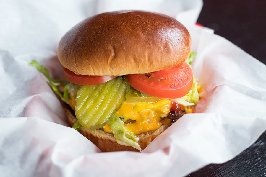 The triple Angus burger comes with caramelized onions, pickles and cheese. - MABEL SUEN