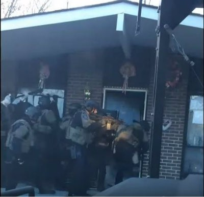 St. Louis County Police Officers gather at the door of Sheila Huck moments before the fatal shooting. - IMAGE VIA YOUTUBE