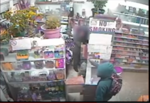 A robber in a green hoodie pulls a gun on a 63-year-old clerk at Asian World Market. - IMAGE VIA ST. LOUIS METROPOLITAN POLICE DEPARTMENT