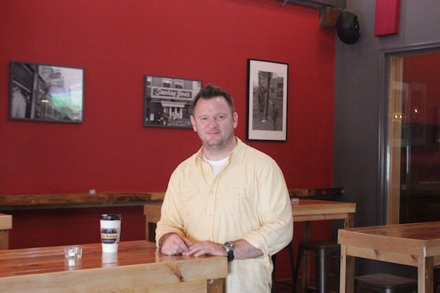 Co-owner JB Anderson, with photos of Gaslight Square behind him. - PHOTO BY SARAH FENSKE