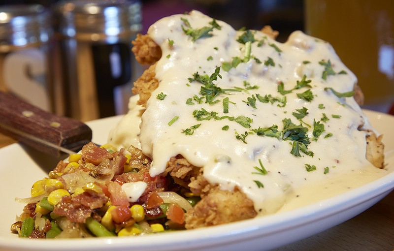 The chicken-fried steak combines hand-battered chicken, garlic mashed potatoes with jalapeno cream gravy and sauteed green beans. - PHOTO BY STEVE TRUESDELL