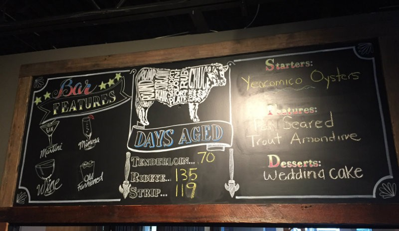 A chalkboard lists the day's cuts of meat. - PHOTO BY EMILY MCCARTER