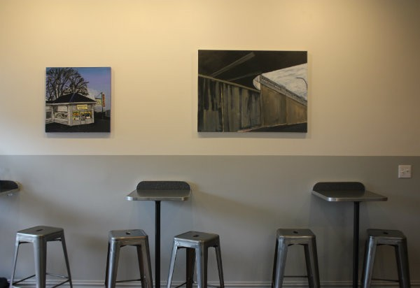 Artwork featuring iconic local spots decorates the walls. - CHERYL BAEHR