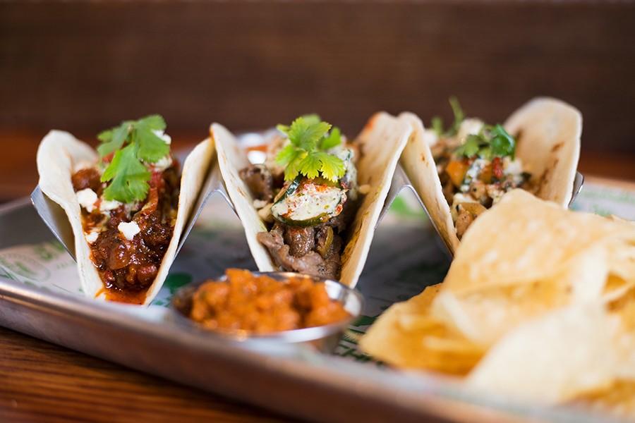 Tacos are topped with cucumber kimchi, cilantro, queso fresco and cilantro mayo. - MABEL SUEN