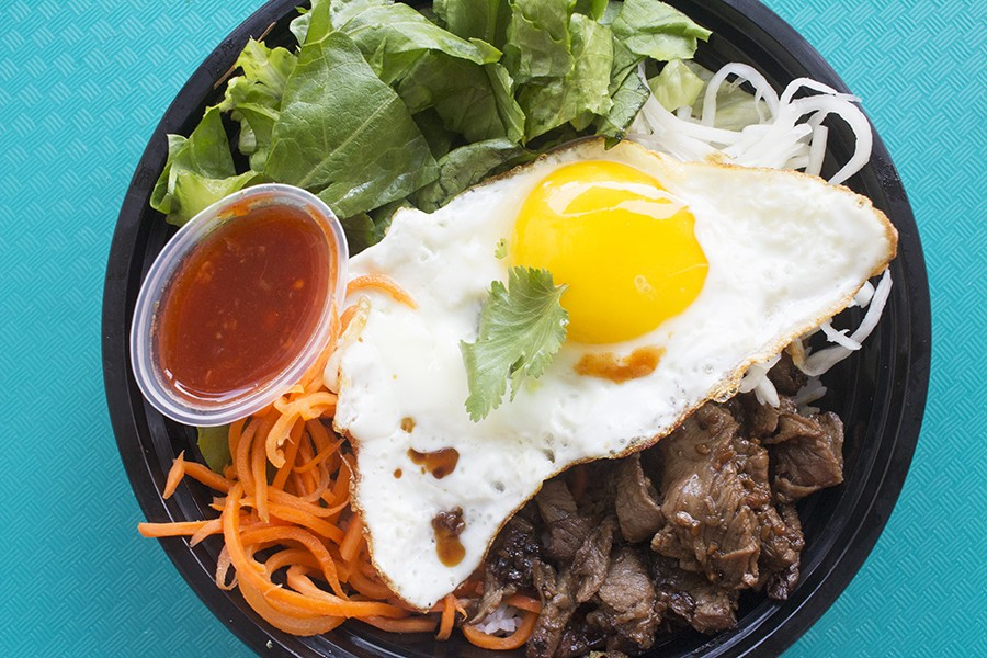 The boneless beef short rib rice bowl is served with with jasmine rice, romaine, sweet pickled carrots, pickled daikon, a fried egg and chili sauce. - PHOTO BY MABEL SUEN