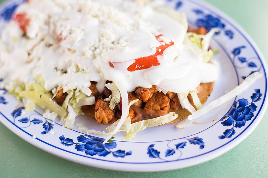 The sope's masa basa soaks in the juices of its toppings — in this case, chicken with pinto beans, lettuce, tomatoes and sour cream. - MABEL SUEN