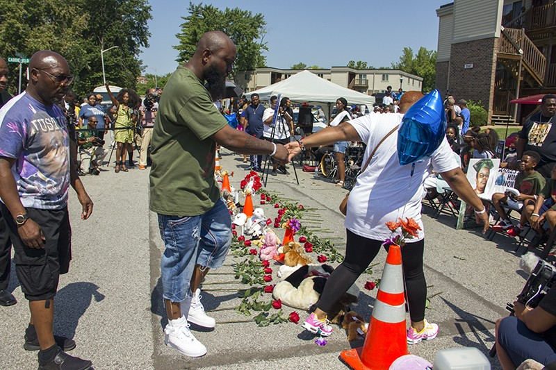 Cal Brown holds the hand of Michael Brown Sr. at their son's memorial on Canfield Drive. - DANNY WICENTOWSKI