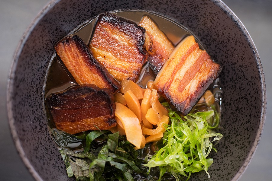 An updated version of pork and beans features braised bacon, Missouri pinto beans in foraged spicebush broth, peach miso, shiso and pickled peaches. - MABEL SUEN