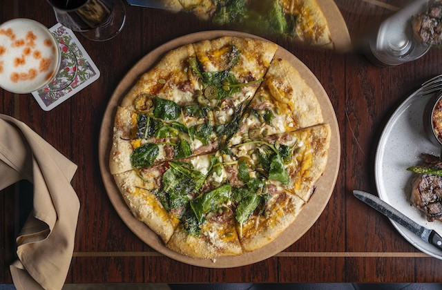 The butternut squash pizza features the root vegetable with a sweet potato puree, crispy country ham, baby kale, pickled jalapeños, pepitas, pomegranate molasses and feta from Baetje Farms. - COURTESY OF LODGING HOSPITALITY MANAGEMENT