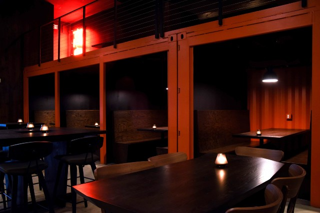 The ground-floor seating area features tables and six booths forged around shipping containers. - TRENTON ALMGREN-DAVIS